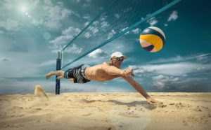 Man Diving on Sand Playing Volleyball